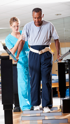 Image of woman helping Man undergoing gait training physical therapy