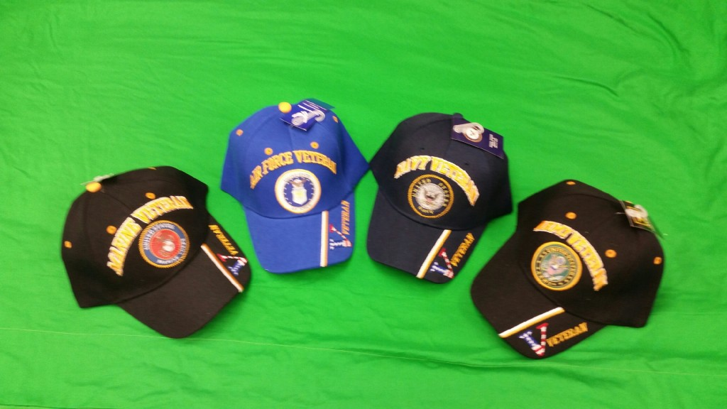 Four hats arraigned in semi-circle with Armed Forces seals and Veteran written on the bill.